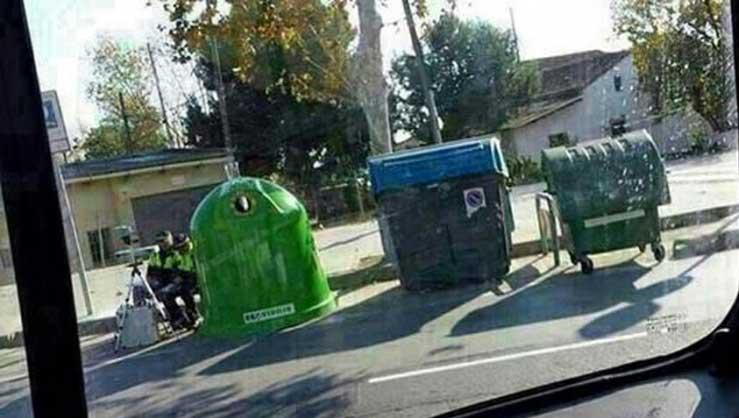 Dos agentes sitúan un radar entre contenedores de basura